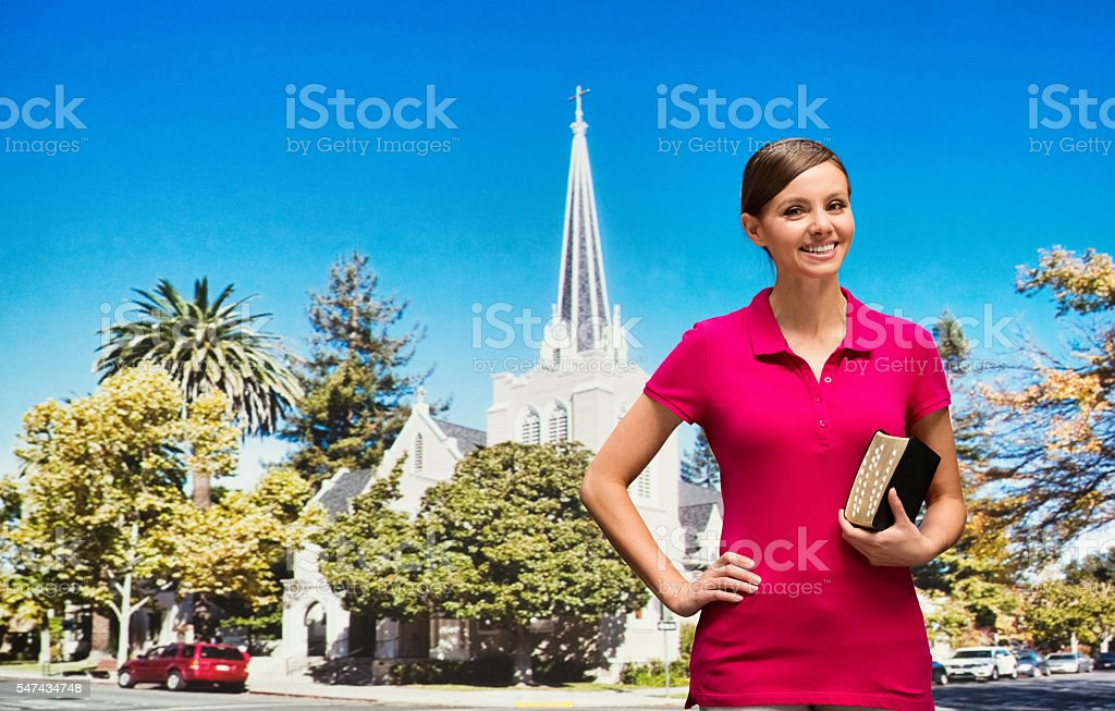 Worshipper in front of church with bible stock photo