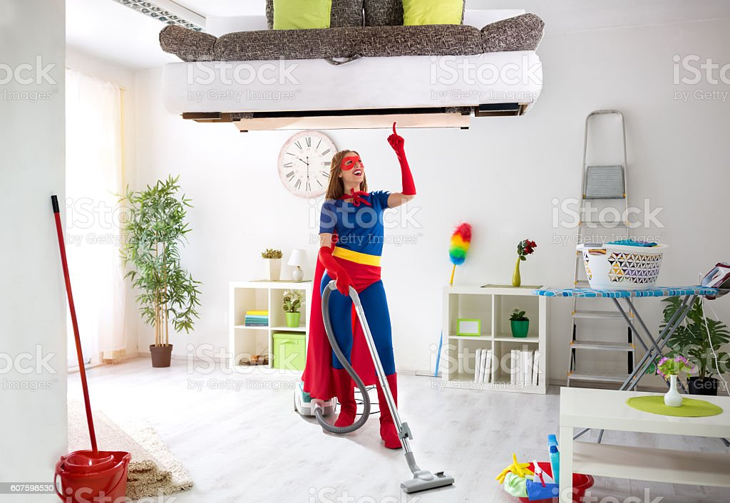 Worth super hero woman in costume use vacuum cleaner stock photo