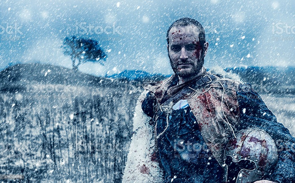 Wounded warrior holds a bloody helmet on the battlefield stock photo