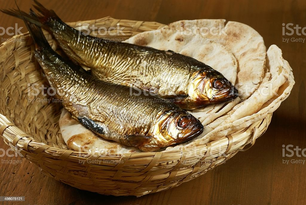 Woven basket of whole fish and flatbread stock photo