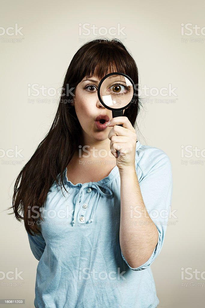 Wow, look at that! Young woman with magnifying glass royalty-free stock photo