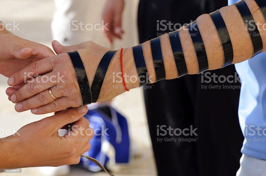 wrap tefillin straps on arm in Judaism stock photo