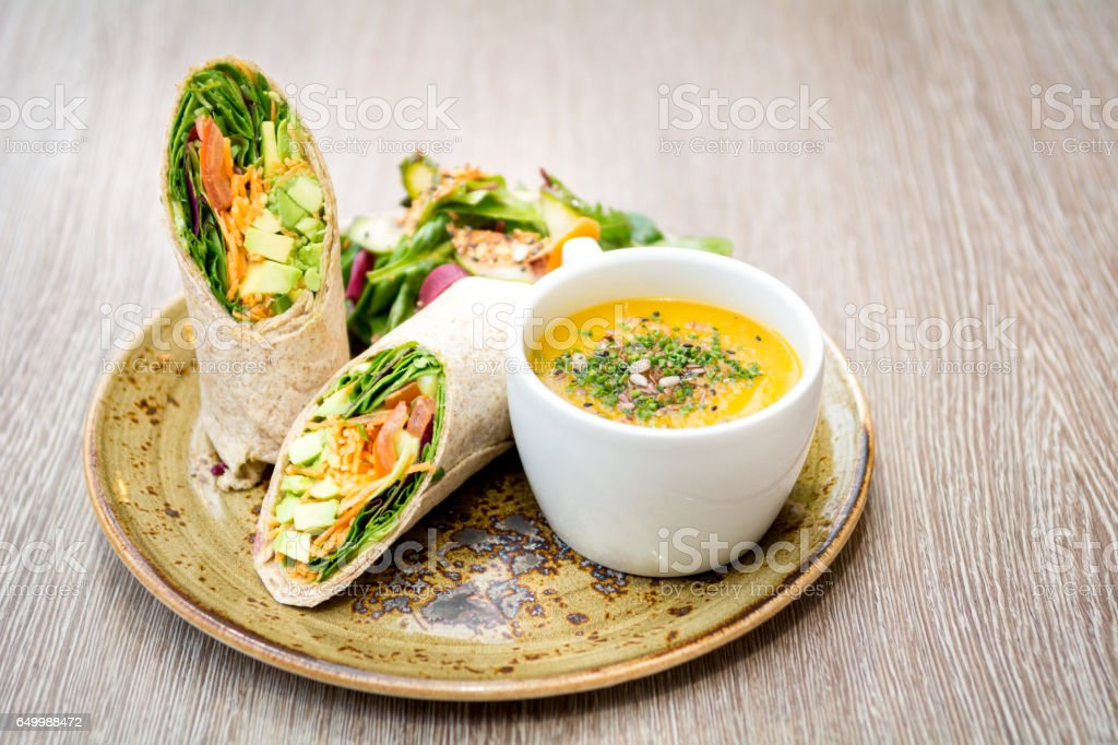 wrap vegetarian sandwich with cup of soup table stock photo