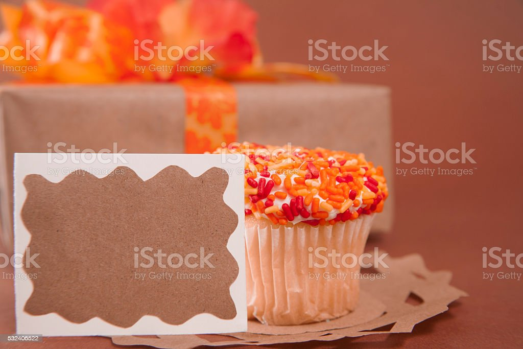 Wrapped gift in browns and orange.  Birthday cupcake. stock photo