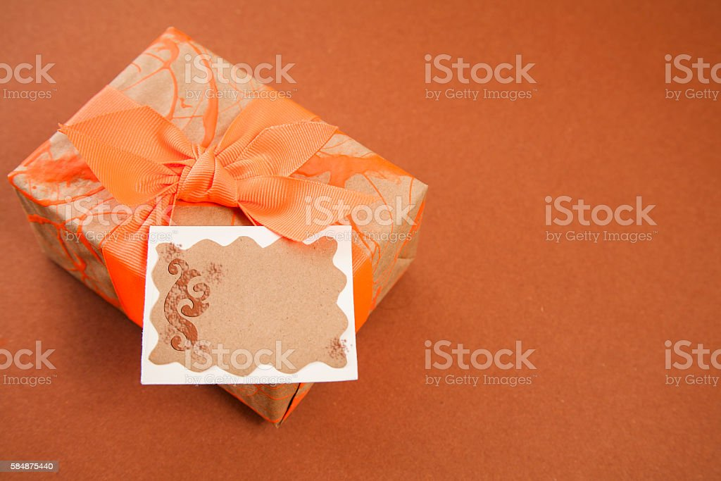 Wrapped gift in browns and orange with blank notecard. stock photo