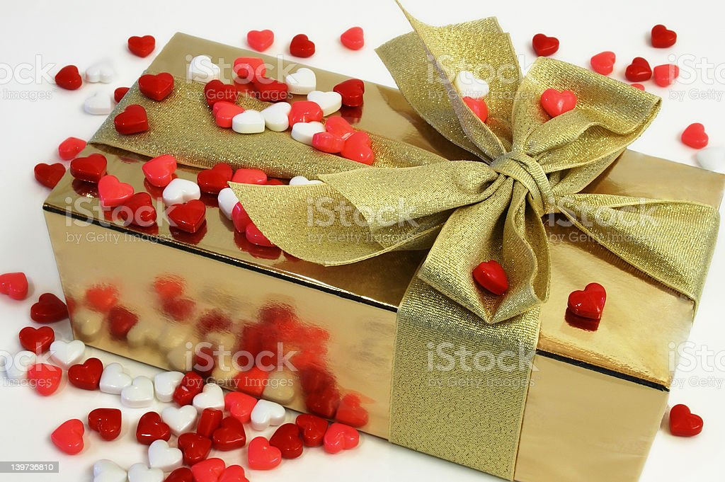 Wrapped Gift Surrounded with Heart Shaped Candies stock photo