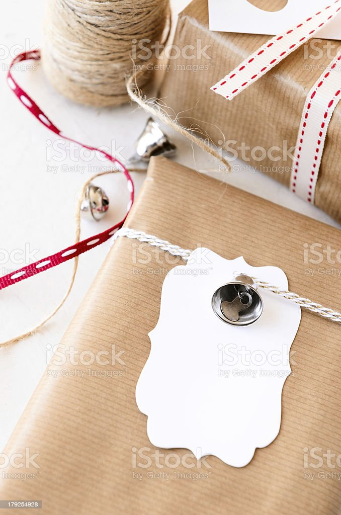 Wrapped gifts decorated with silver bells and gift tags royalty-free stock photo