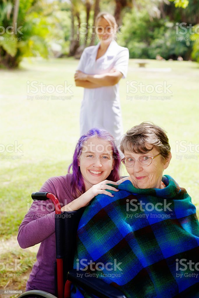 Wrapped-up old woman smiles impishly with granddaughter, nurse behind them stock photo