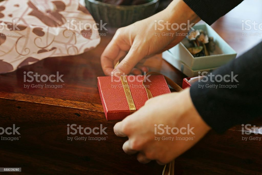Wrapping red gift with ribbon on wooden table stock photo