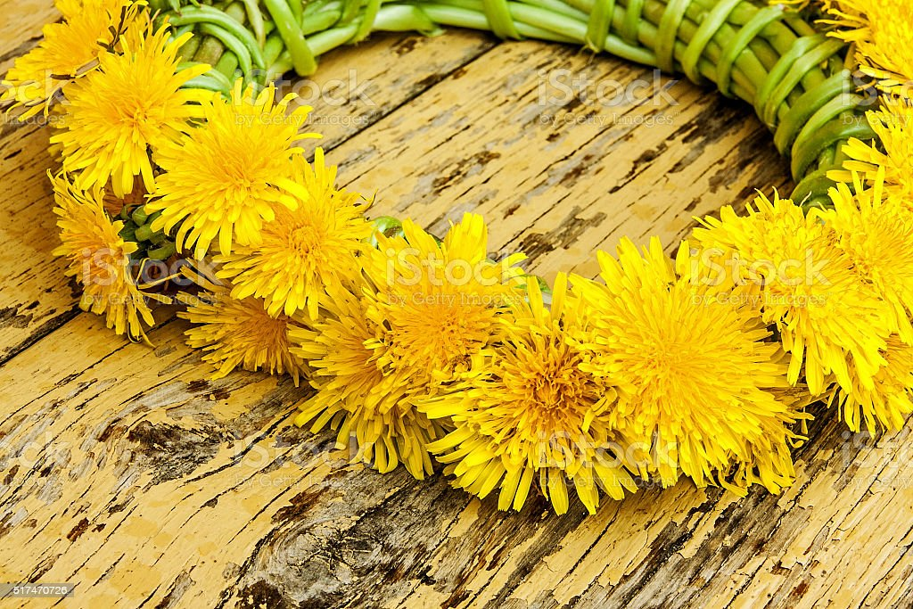 Wreath from dandelions on a wooden surface stock photo