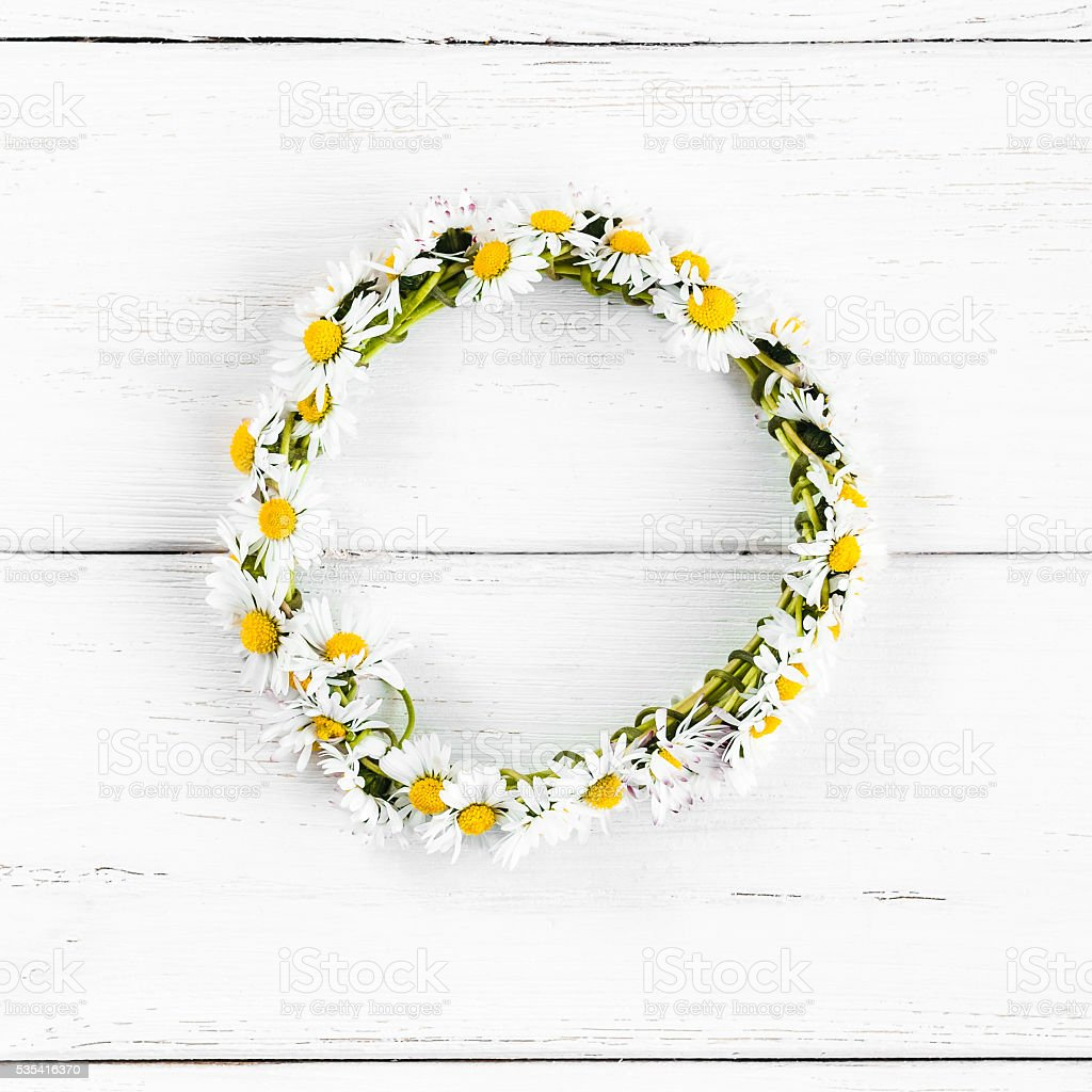 wreath made of daisy flowers on white wooden background stock photo