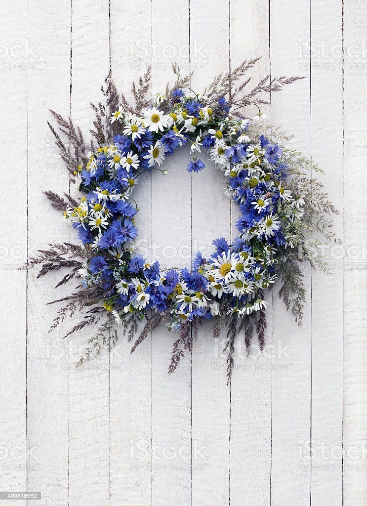 Wreath of flowers on the white wooden background stock photo