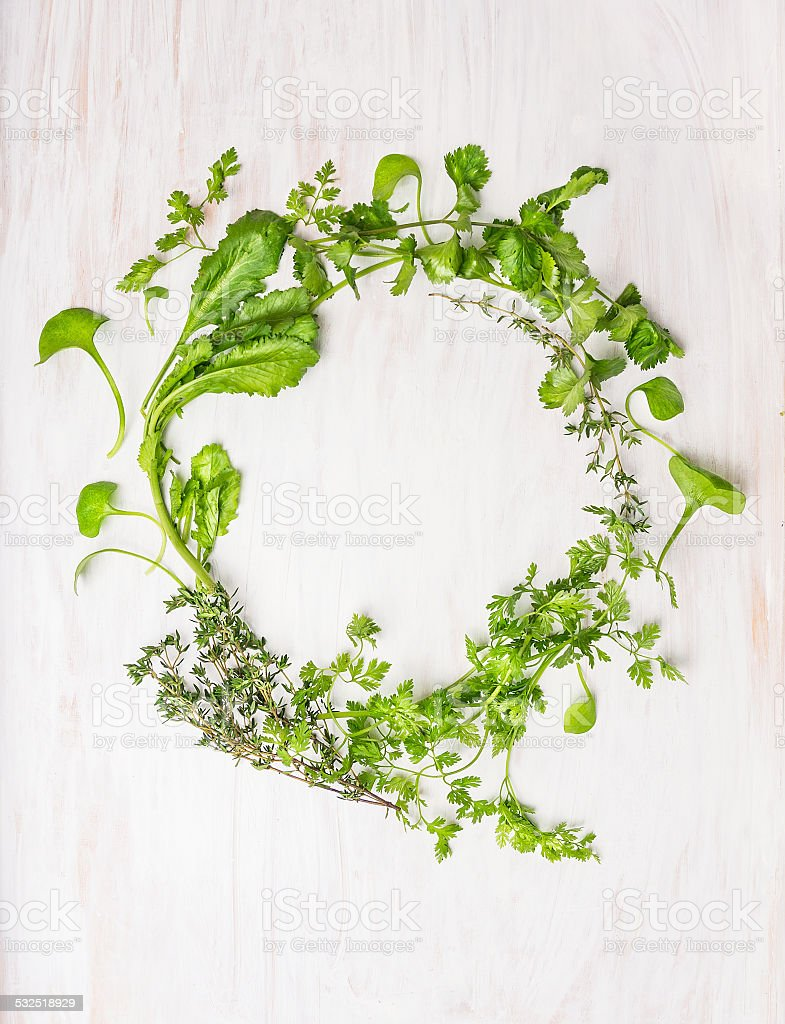 wreath of green herbson white wooden background, top view stock photo
