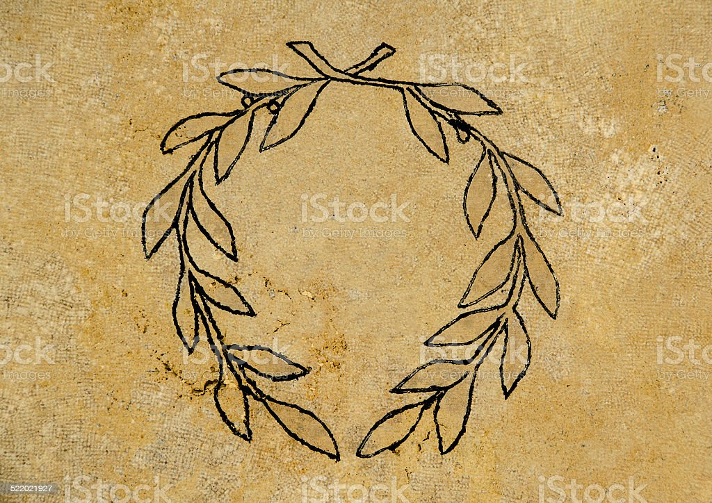 Wreath of olive symbol over yellow wall stock photo