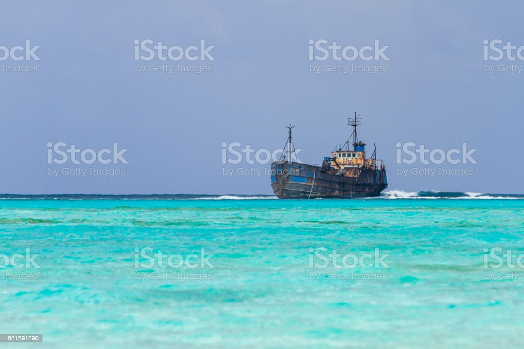 Wreck aground over reef stock photo