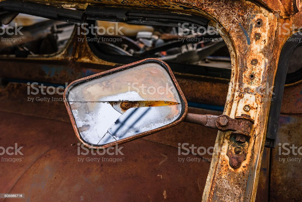 Wreckage side mirror of an rusty car in garage stock photo