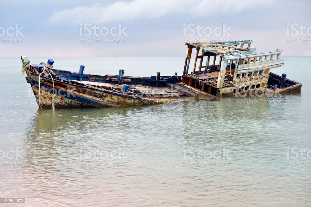Wrecked boat abandoned stand on beach Thailand . stock photo