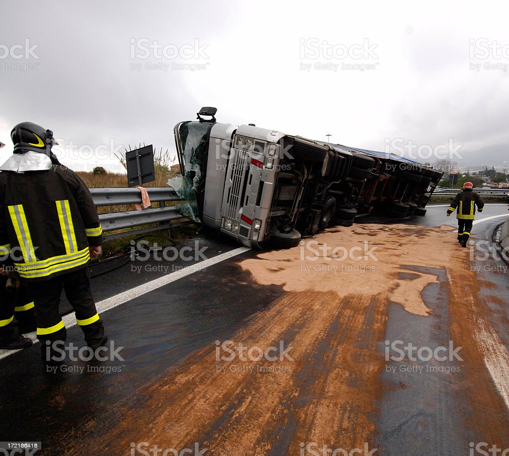 Wrecked gray overturned bus on the side of the road stock photo