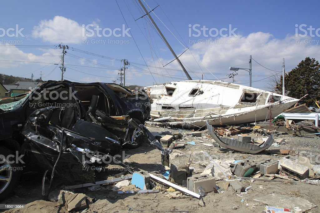 A wrecked sailboat amid rubble from an Japanese earthquake stock photo