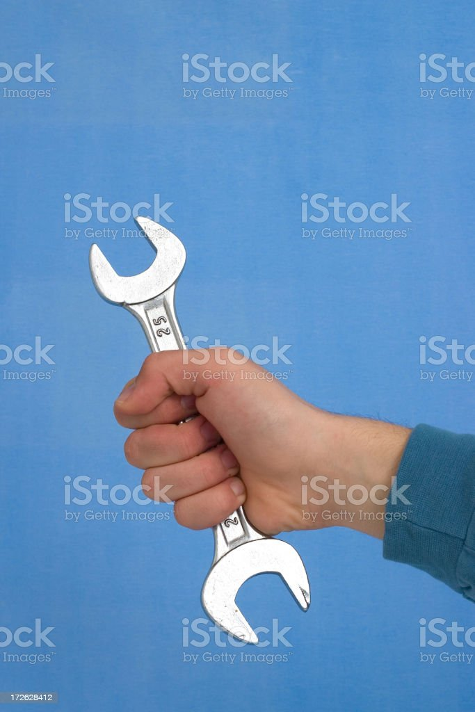Wrench in hand, blue background royalty-free stock photo