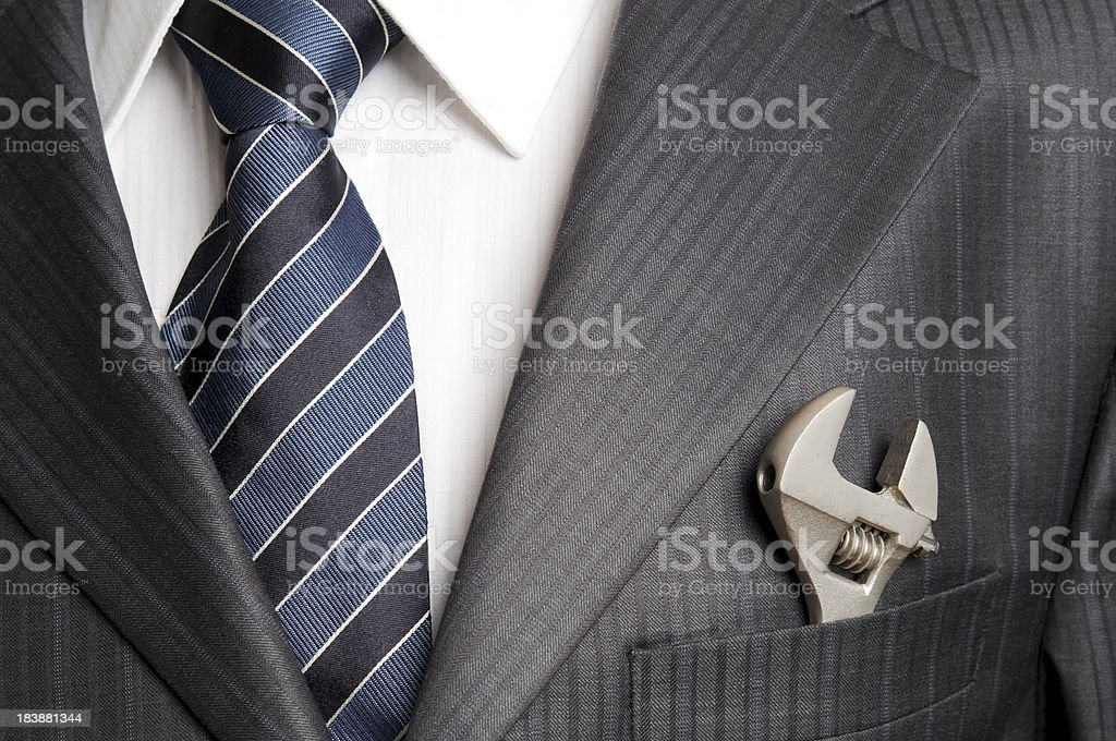 Wrench in pocket of businessman stock photo