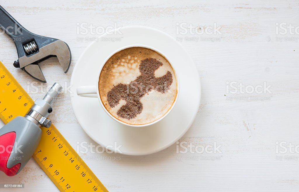 Wrench made of cinnamon powder in cappuccino. Repair service concept. stock photo
