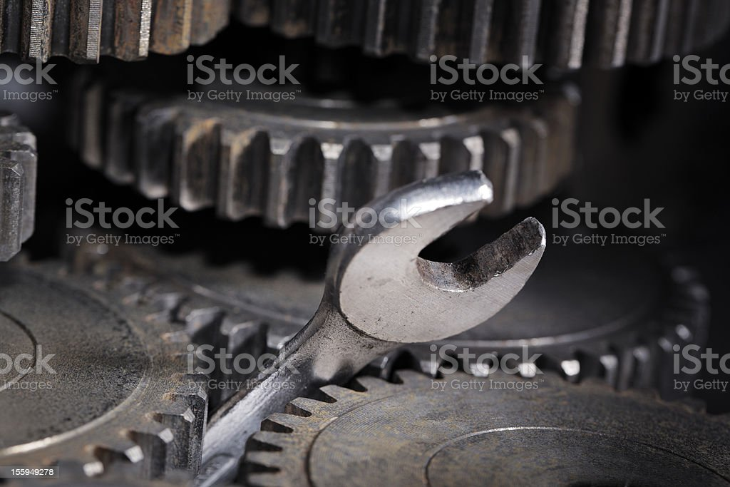 A wrench stuck in the middle of some gears stock photo