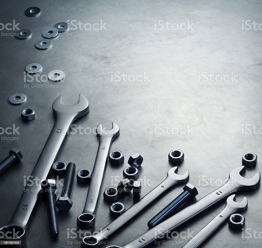 Wrenches, nuts and screws on a metal plate stock photo
