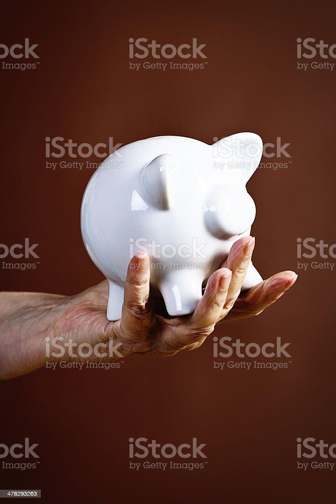Wrinkled hand holding piggybank royalty-free stock photo