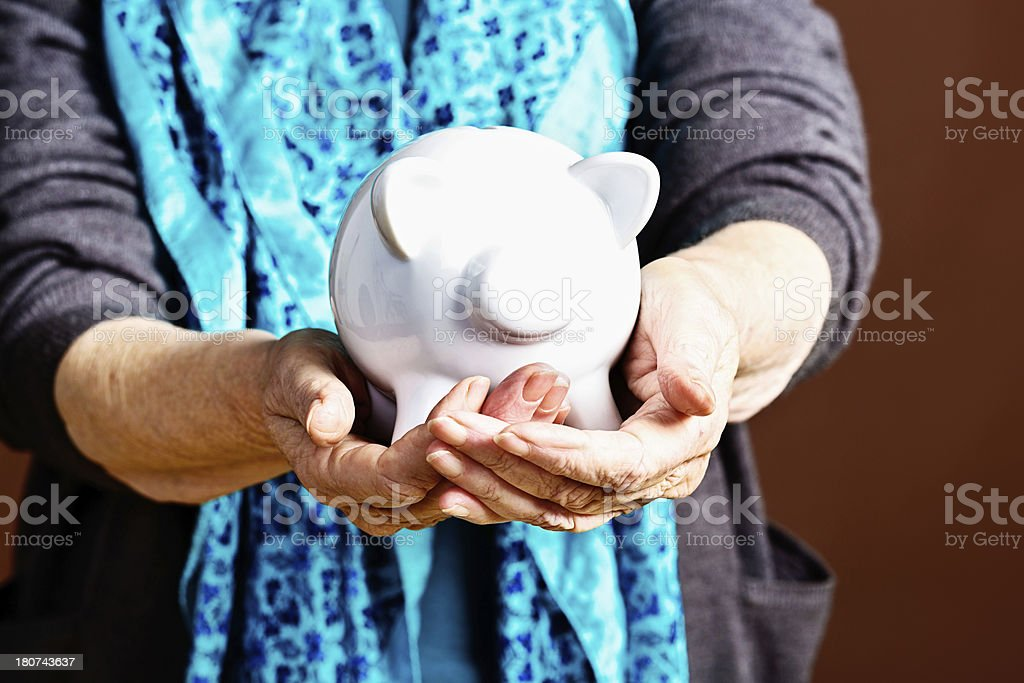 Wrinkled hands hold out piggybank; she's not making ends meet royalty-free stock photo
