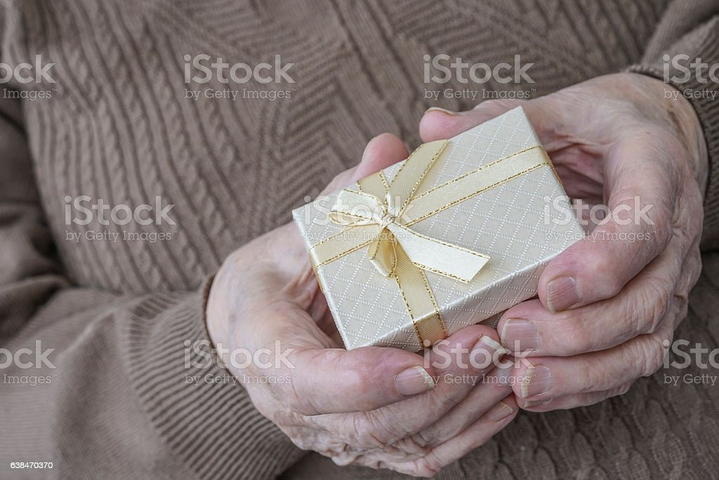 wrinkled hands holding gift stock photo