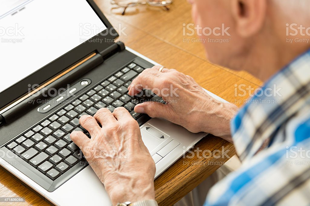 Wrinkled hands typing on computer keyboard royalty-free stock photo