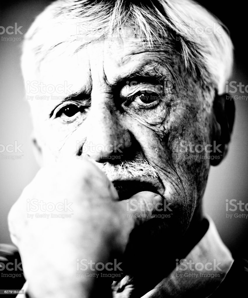 Wrinkled old man faces the world in black and white stock photo