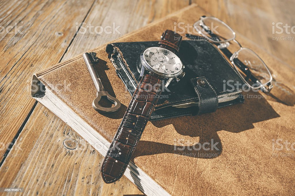 Wristwatch, calendar, key and glasses on table stock photo