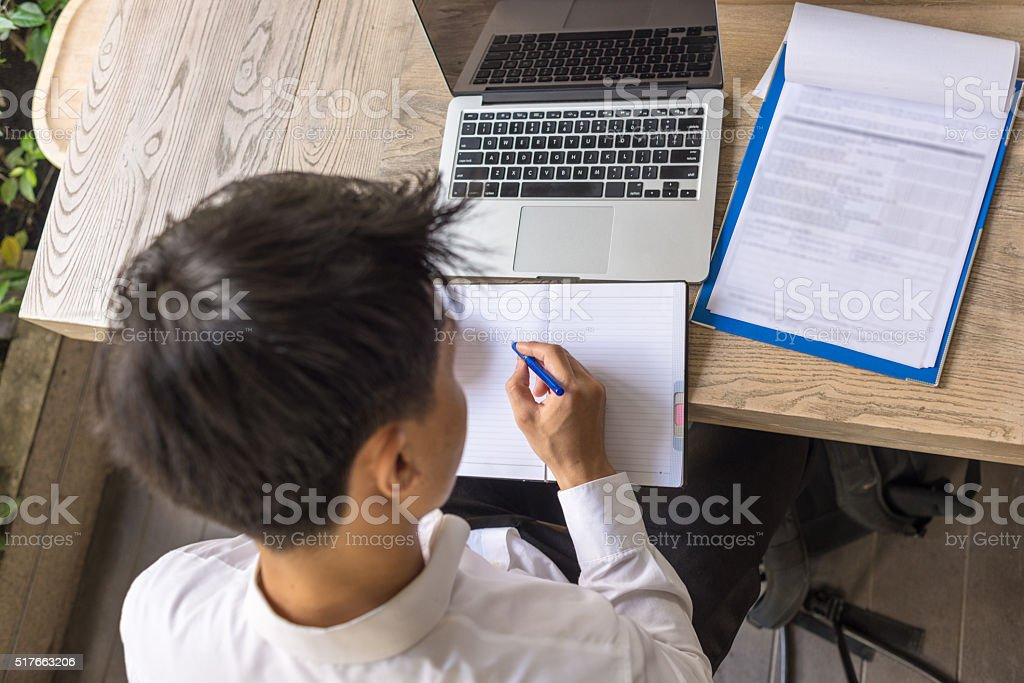Write down important information from sales report to his notebook stock photo