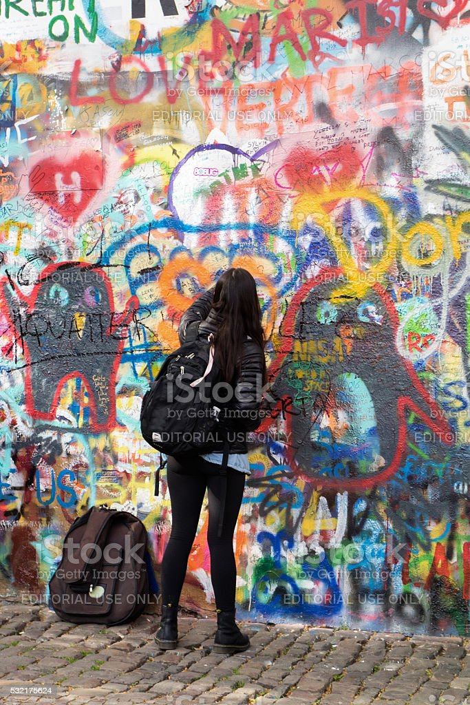 Writer at work writing on a colorful wall, aka 'Lennon's wall' stock photo