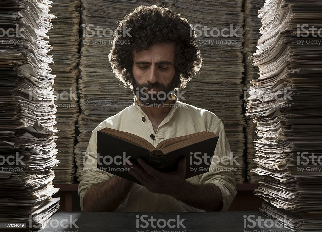 Writer reading book in library among stacks of documents stock photo