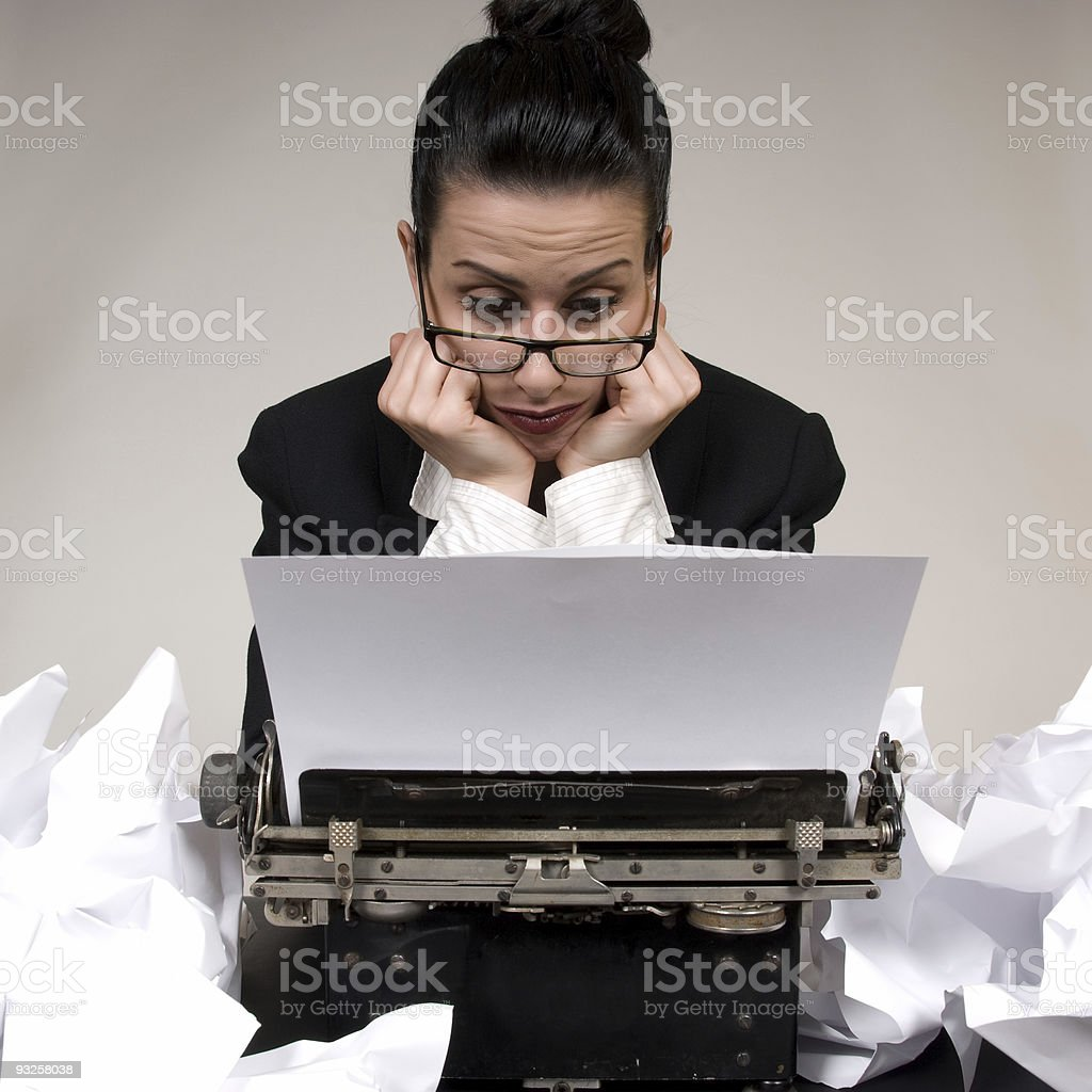 A writer struggling to type more words in her typewriter royalty-free stock photo