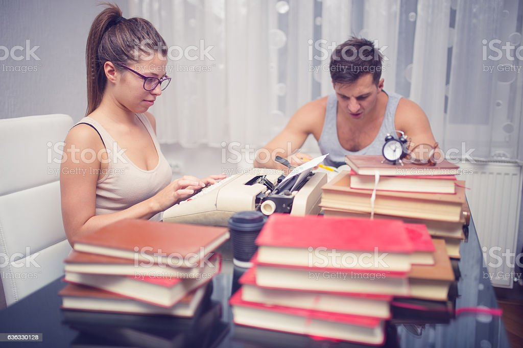 Writers surrounded by books stock photo