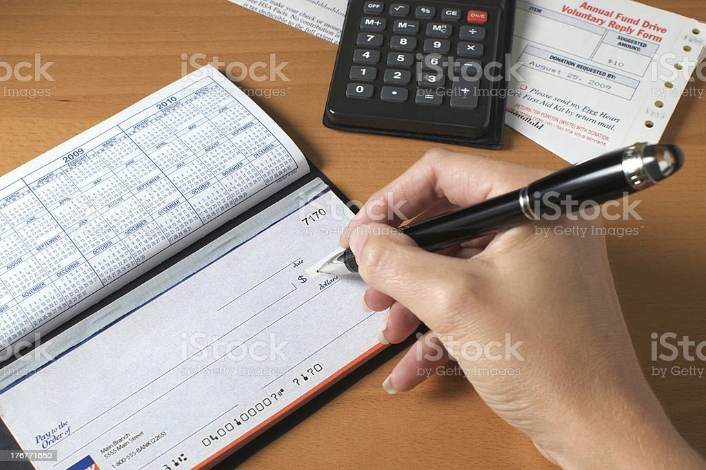 Writing a check to pay the bills, hand holding pen stock photo