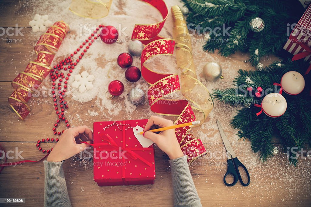 Writing a message on Christmas present tag stock photo