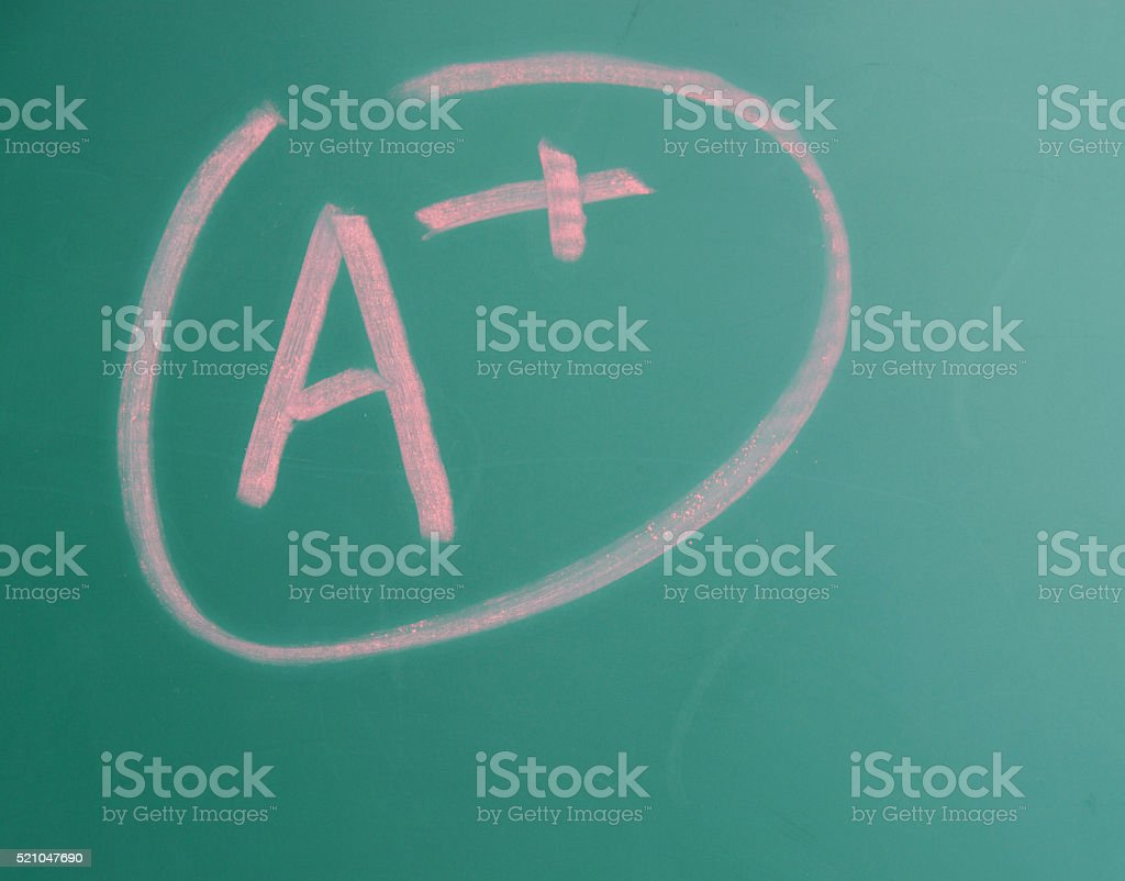Writing A+ on chalkboard stock photo