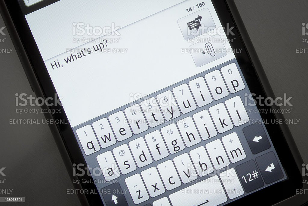 Writing an SMS on mobile phone with touch screen stock photo