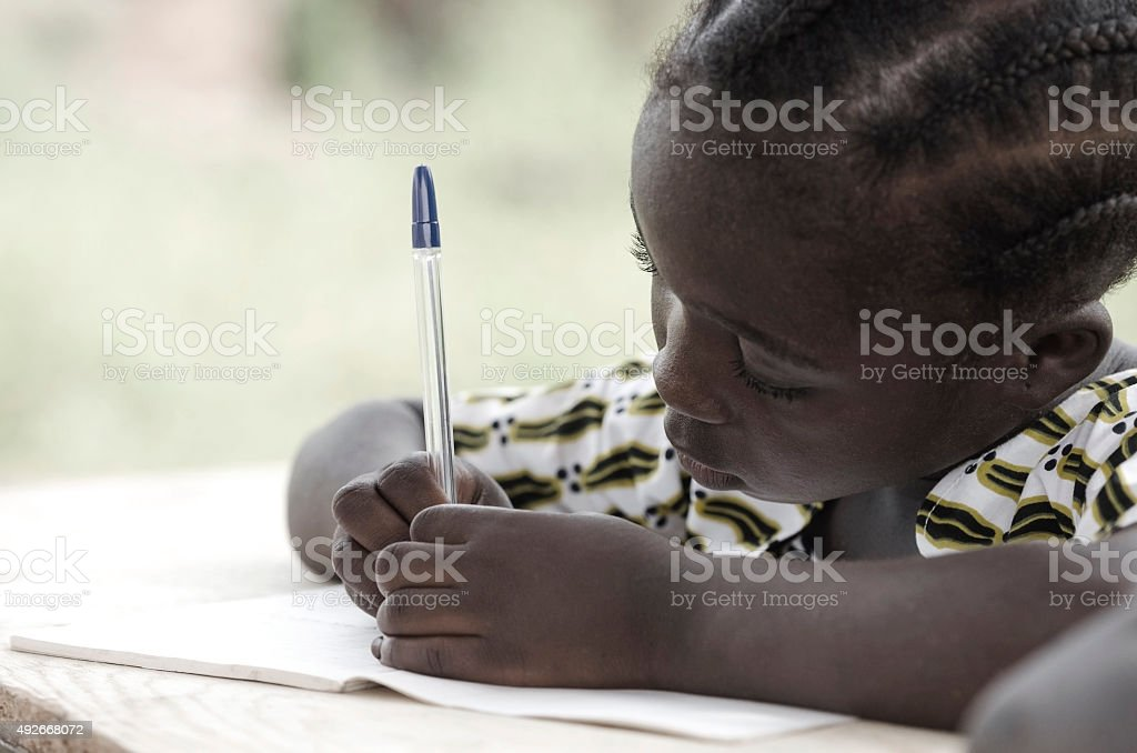 Writing and Learning Symbol: Cute African Schoolgirl Doing Homework stock photo