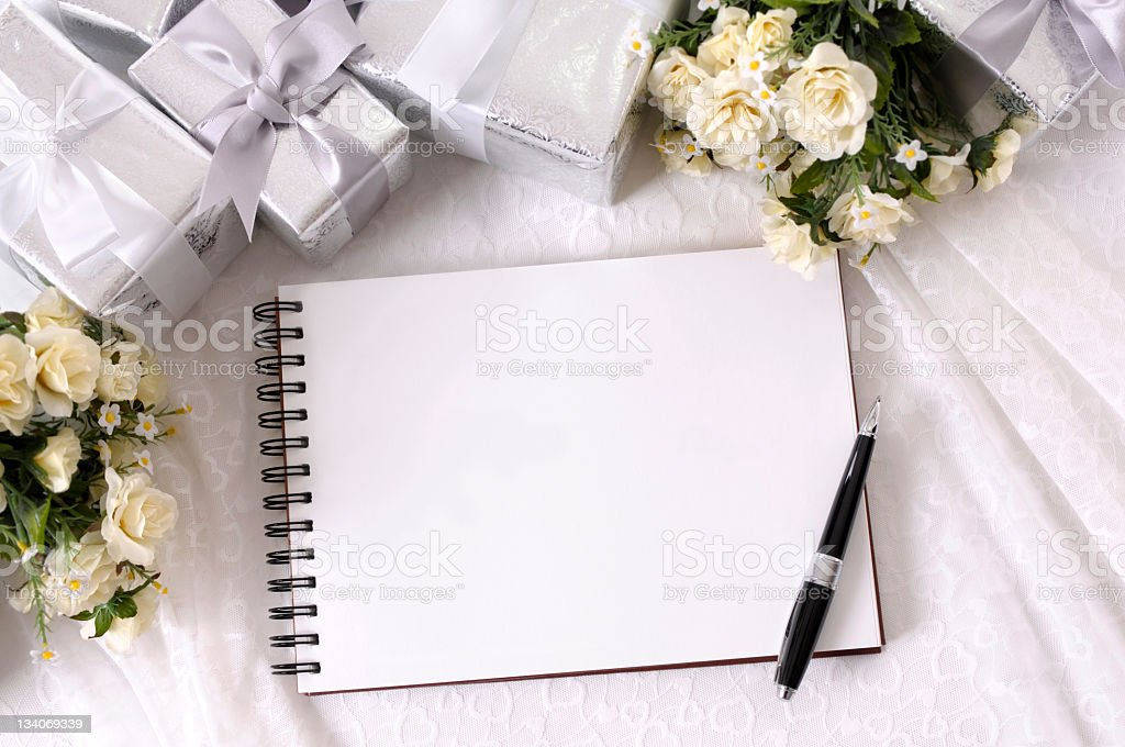 Writing book on table with wrapped wedding gifts and flowers stock photo