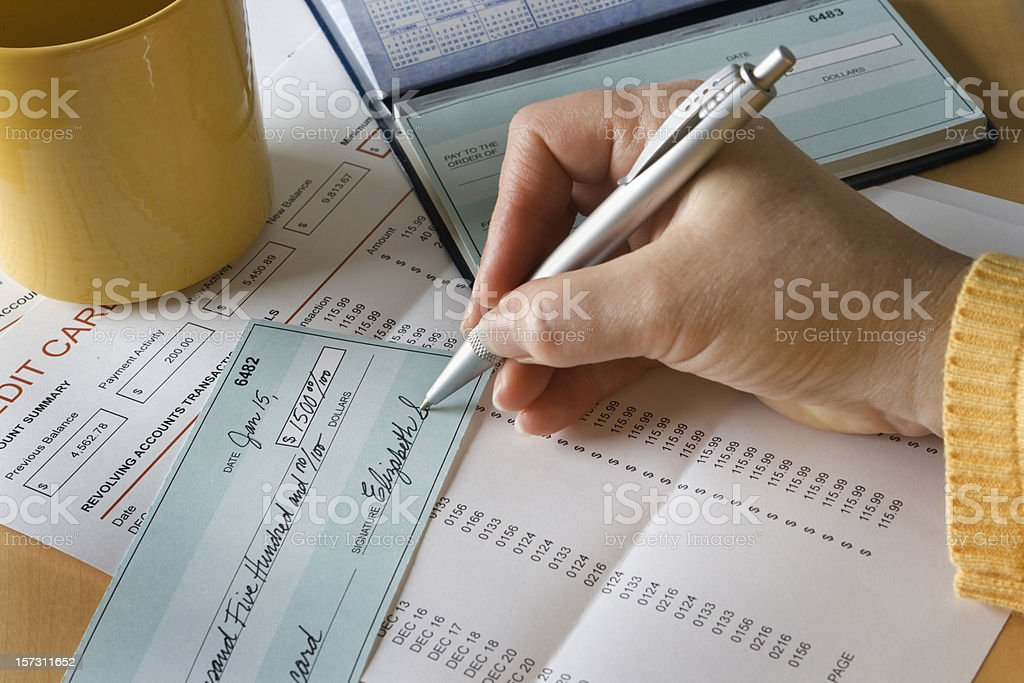 Writing Check Paying Credit Card Debt and Bills for Finance stock photo