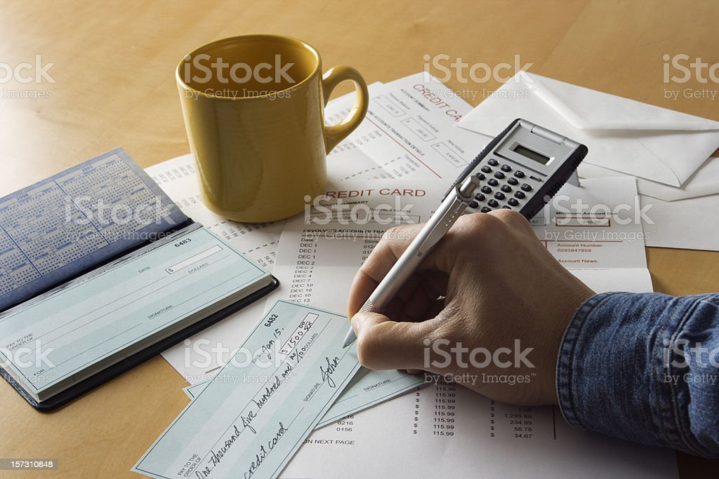 Writing Checks, Paying Bills, and Calculating Home Finances Credit Debts royalty-free stock photo