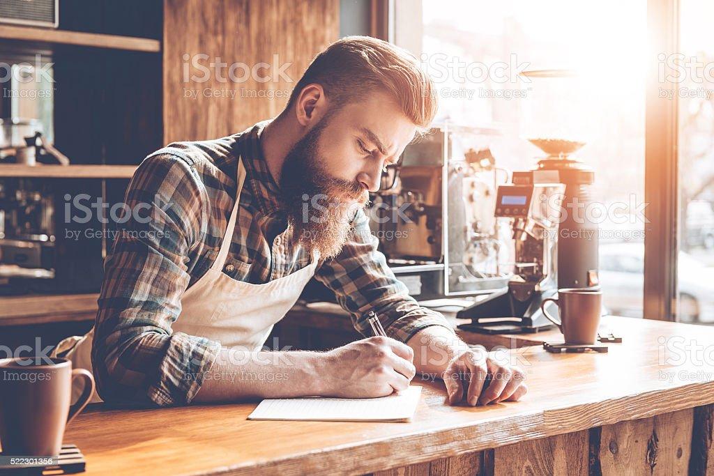 Writing down new coffee recipes. stock photo