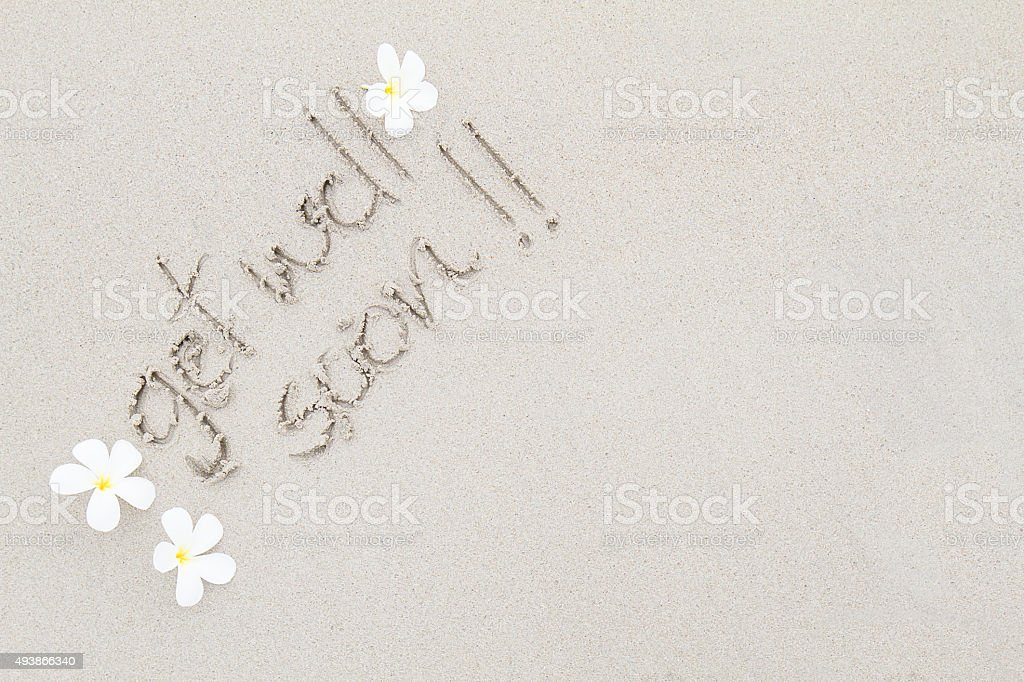 Writing get well soon with white flowers on the beach stock photo