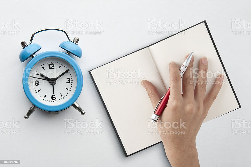 Writing hand and alarm clock royalty-free stock photo